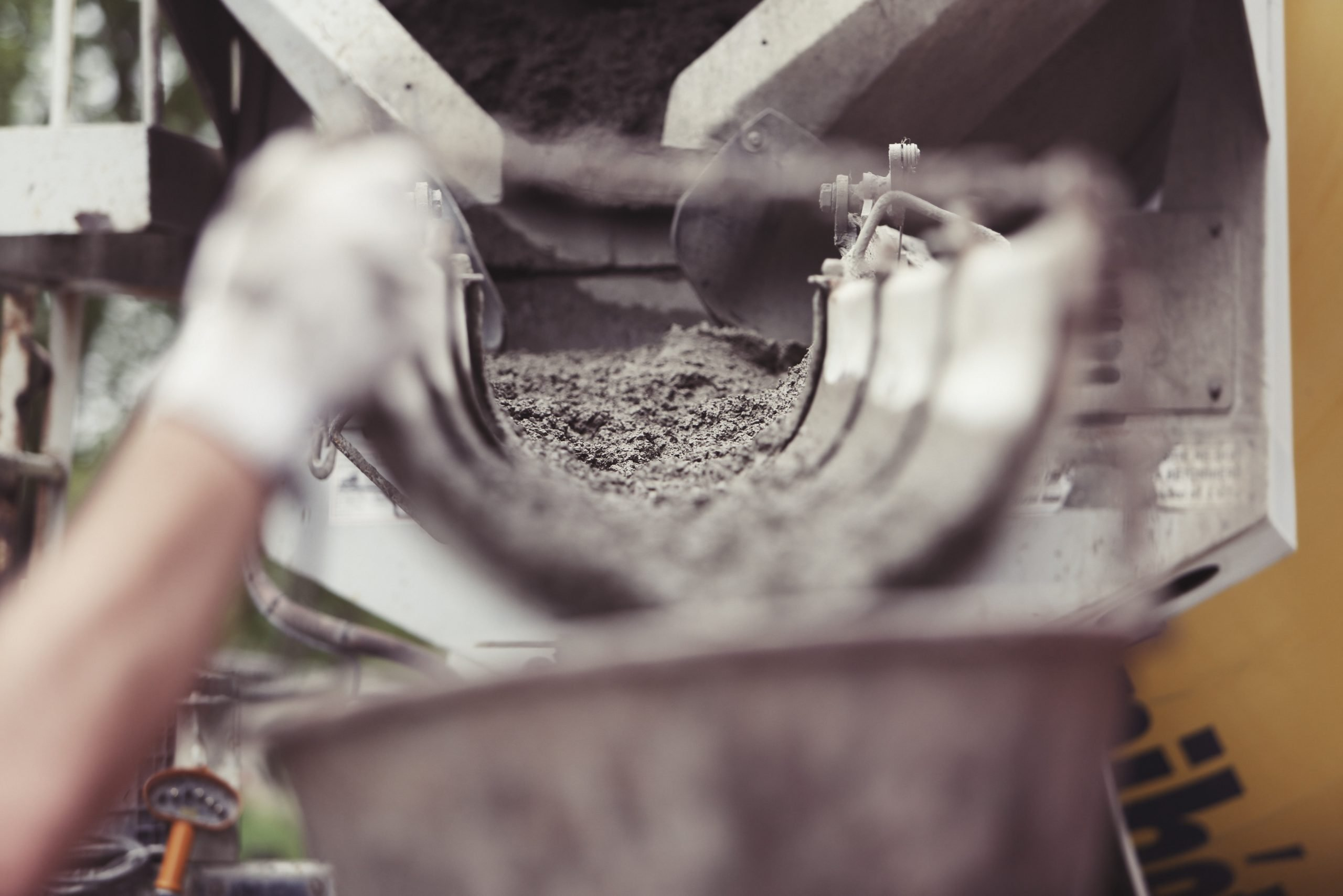 Cement flowing out of a concrete truck at a construction site, showing the start of the concrete lifecycle.