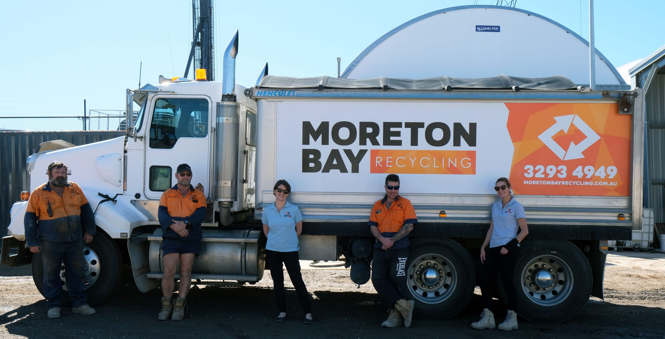 Photo of the Moreton Bay Recycling team standing in front of a truck in the yard, while observing social distancing guidelines.