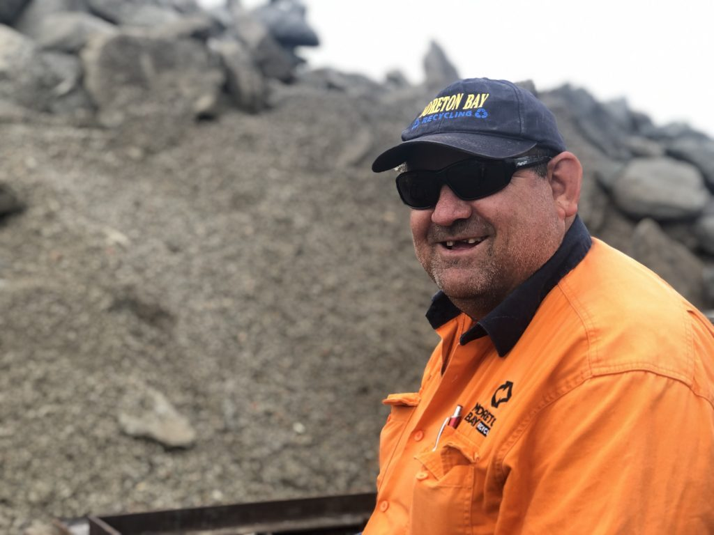Eddie smiles while standing in front of a large pile of concrete aggregate.