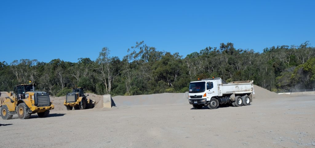 Moreton Bay Recycling's yard shown with three trucks and a boundary lined with trees.