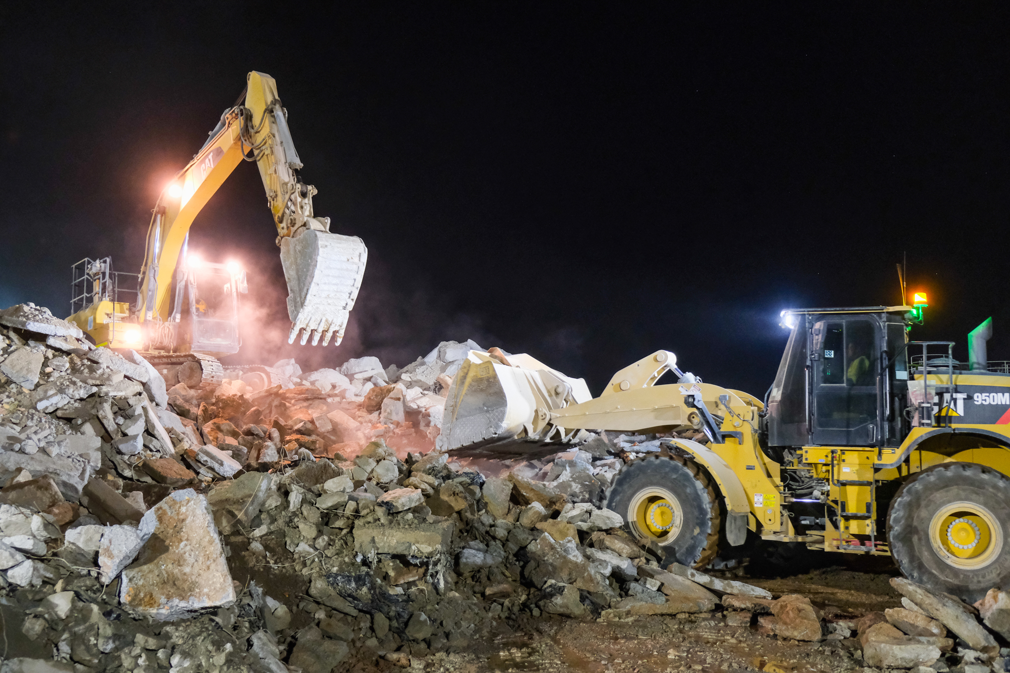 Digger and front wheel loader shown working at night to move concrete waste, ready for recycling.