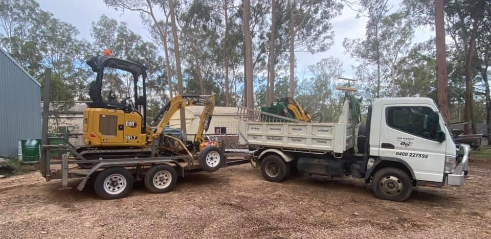 JSB Kanga equipment, including a truck, trailer, and mini excavator.