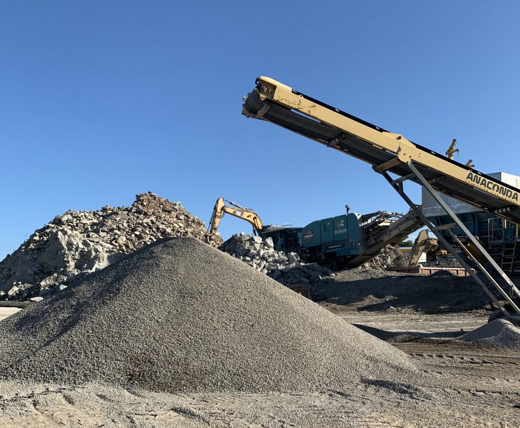 Crushing equipment at Moreton Bay Recycling crushes concrete waste into recycled product. Piles of rubble and aggregates are visible, along with the equipment.
