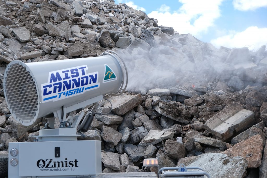 Using a water cannon to wet down the rubble and reduce dust in the yard.