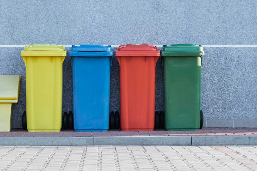 A yellow, blue, red, and green wheelie bin are lined up along a grey wall.