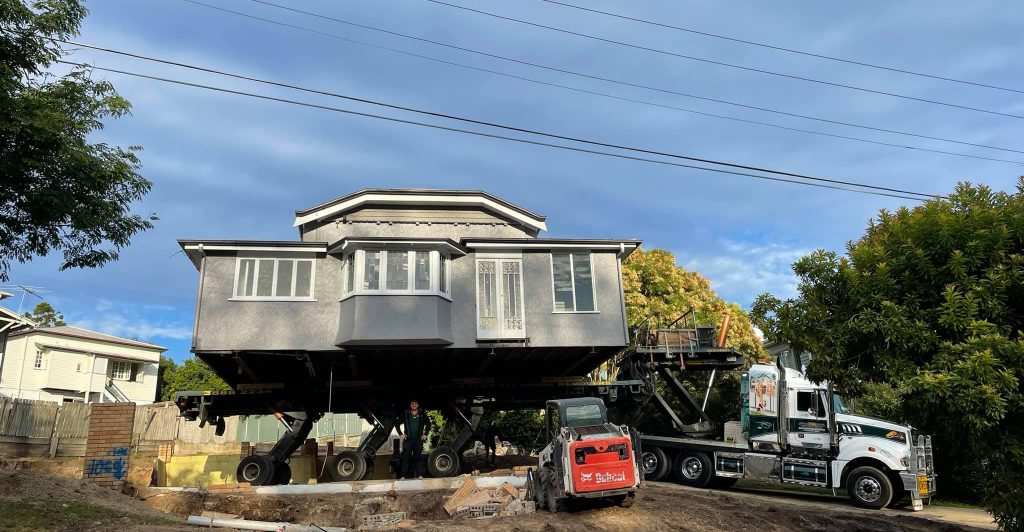 Grey house shown being removed on the back of a truck.