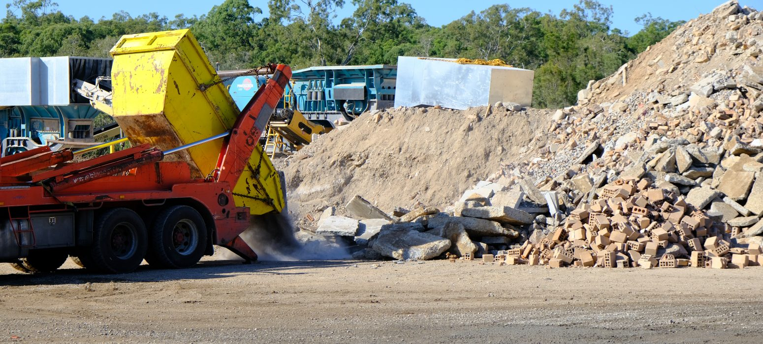 Red truck dumping concrete waste from yellow skip bin