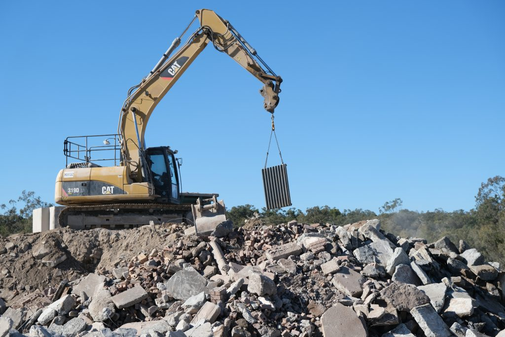 A CAT truck lifts a large piece of aluminium sheeting from a pile of concrete rubble.